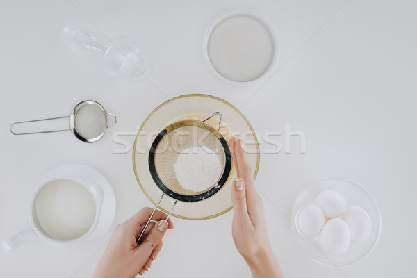 cropped shot of person sifting flour while cooking pancakes isolated on grey Stock photo © LightFieldStudios