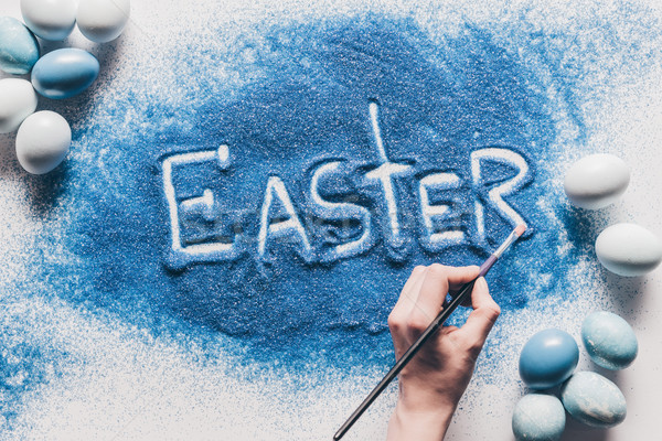 cropped image of woman making easter sign with blue sand on white surface Stock photo © LightFieldStudios