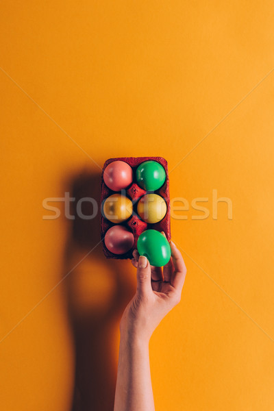 cropped image of woman taking green easter egg from egg tray on orange Stock photo © LightFieldStudios