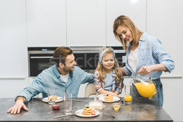 portrait of woman pouring juice into glass during breakfast with family at home Stock photo © LightFieldStudios