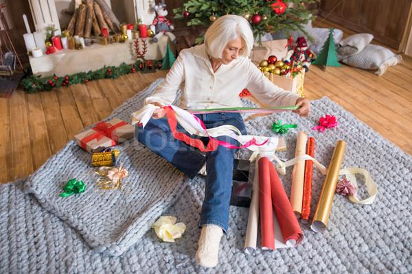 женщину упаковка Рождества представляет старший сидят Сток-фото © LightFieldStudios
