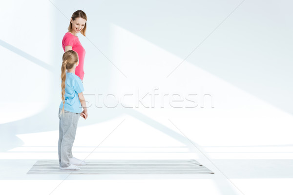 Happy mother and little daughter standing on yoga mat and looking at each other Stock photo © LightFieldStudios