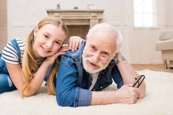 Happy little girl and senior man with eyeglasses lying together on carpet and smiling at camera Stock photo © LightFieldStudios