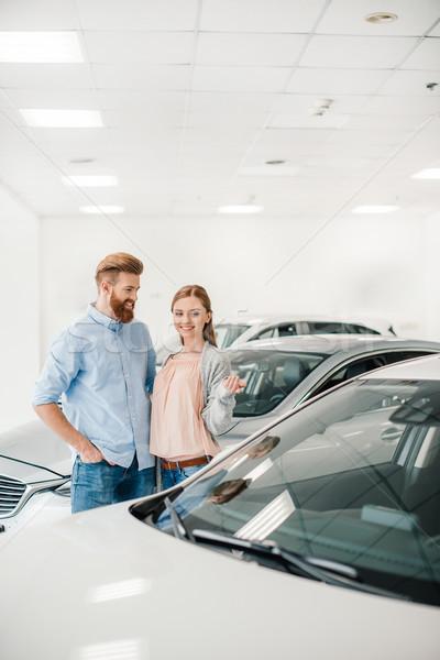 Happy couple choosing car in dealership salon, woman pointing on car Stock photo © LightFieldStudios