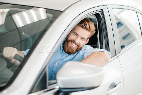 улыбаясь бородатый молодым человеком сидят Новый автомобиль глядя Сток-фото © LightFieldStudios