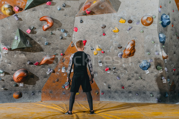 young man in front of climbing wall Stock photo © LightFieldStudios
