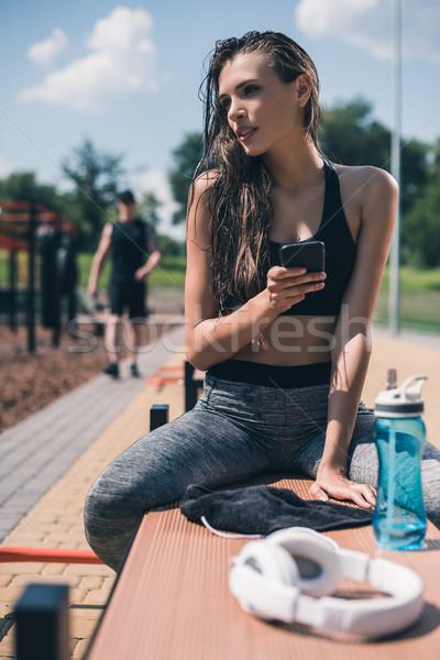 sportive woman with smartphone Stock photo © LightFieldStudios