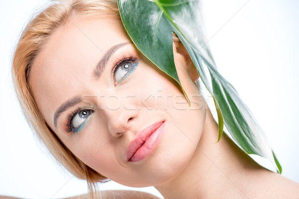 Attractive young woman with green leaf on head smiling and looking up, skincare concept Stock photo © LightFieldStudios