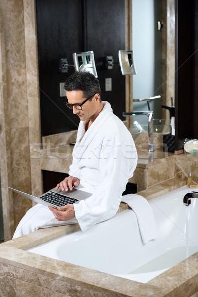 üzletember fürdőköpeny laptopot használ visel hotel fürdőszoba Stock fotó © LightFieldStudios