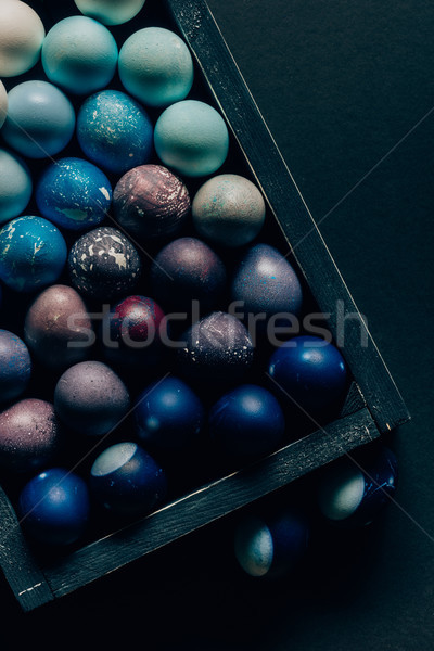 top view of colored painted easter eggs in wooden box on dark table Stock photo © LightFieldStudios