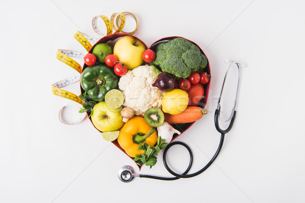 vegetables and fruits laying in heart shaped dish near stethoscope and measuring tape isolated on wh Stock photo © LightFieldStudios