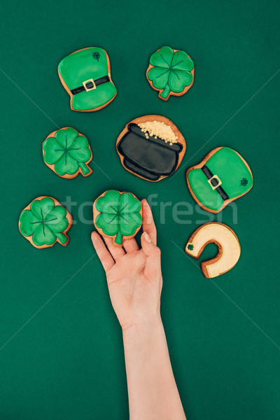 cropped image of woman holding icing cookies isolated on green, st patricks day concept Stock photo © LightFieldStudios