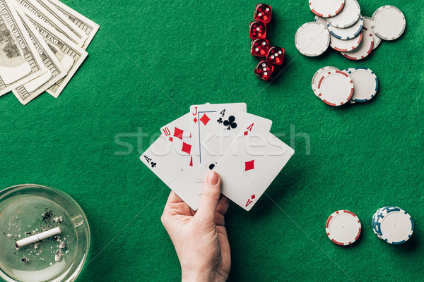 Female hand holding playing cards by casino table Stock photo © LightFieldStudios
