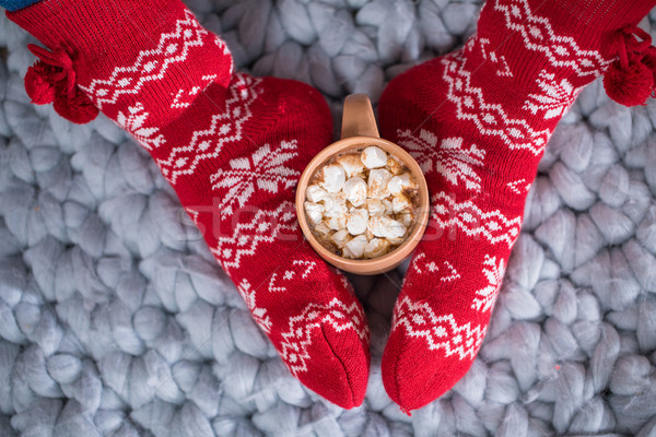 Female feet and cup with hot chocolate  Stock photo © LightFieldStudios