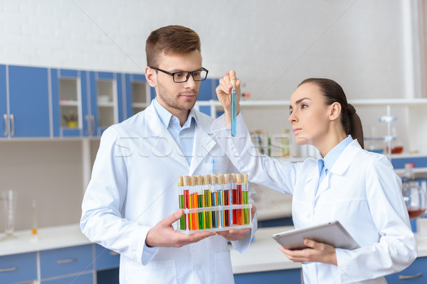 Professional chemists in white coats inspecting test tube with reagent in lab Stock photo © LightFieldStudios