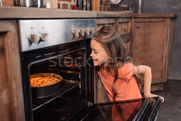 'side view of smiling girl looking at cake in oven in kitchen Stock photo © LightFieldStudios