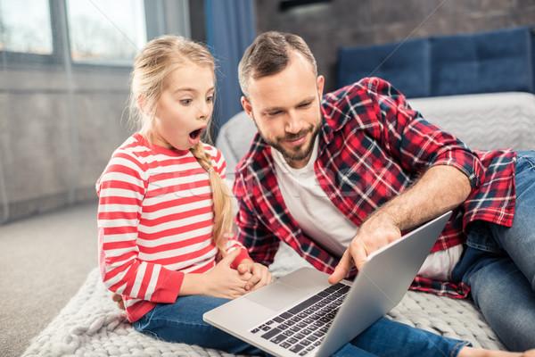 Pai filha usando laptop jovem surpreendido casa Foto stock © LightFieldStudios