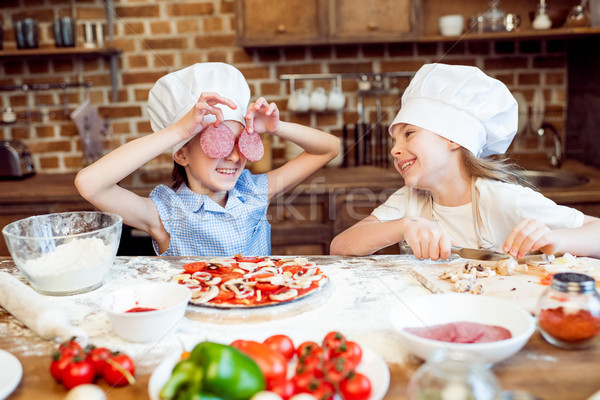 Stock photo: kids in chef hats having fun while making pizza