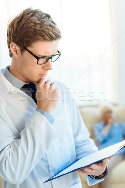 Doctor reading notes on clipboard Stock photo © LightFieldStudios