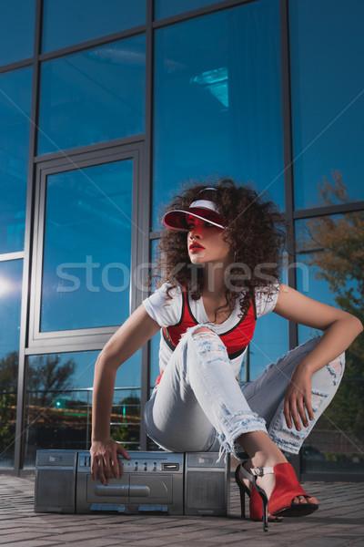 attractive woman sitting on boombox Stock photo © LightFieldStudios