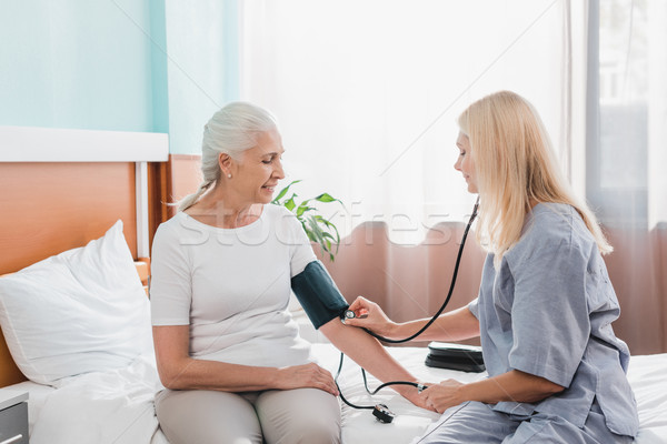 Verpleegkundige bloeddruk patiënt glimlachend senior Stockfoto © LightFieldStudios