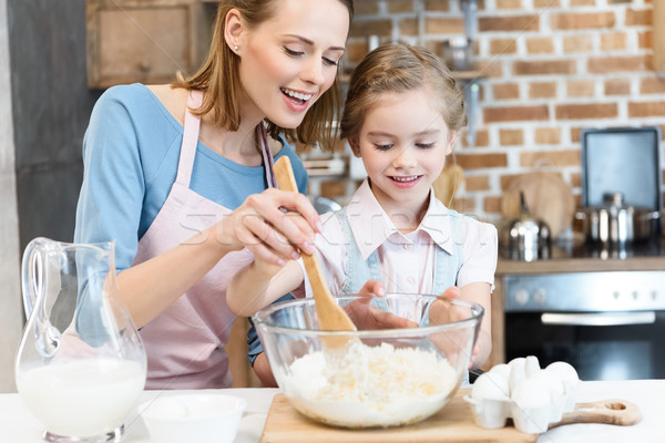 Happy mother and daughter mixing dough in glass bowl for home baking Stock photo © LightFieldStudios