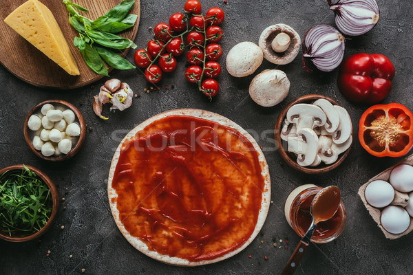 top view of uncooked pizza dough with sauce and vegetables on concrete table Stock photo © LightFieldStudios