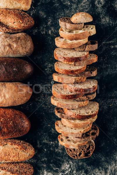 top view of arranged loafs and pieces of bread on dark tabletop Stock photo © LightFieldStudios