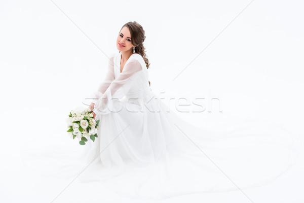 Stock photo: smiling bride in elegant dress holding wedding bouquet, isolated on white