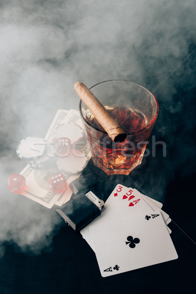 Glass with whiskey and cigar on table with cards and money Stock photo © LightFieldStudios