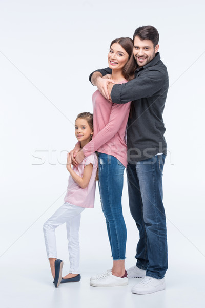 Happy family with one child standing together and hugging on white Stock photo © LightFieldStudios