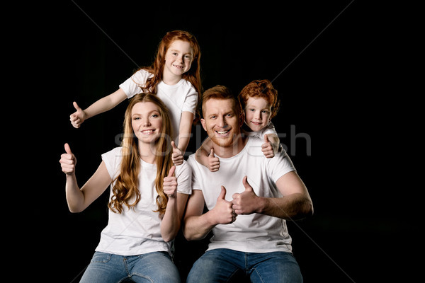 portrait of happy family showing thumbs up isolated on black Stock photo © LightFieldStudios
