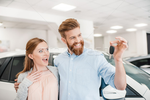 excited couple holding car key and standing at car in dealership salon    Stock photo © LightFieldStudios