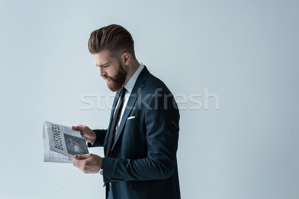 Stylish bearded businessman reading newspaper on grey Stock photo © LightFieldStudios