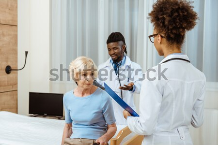 Stock photo: Doctor helping elderly woman with cane