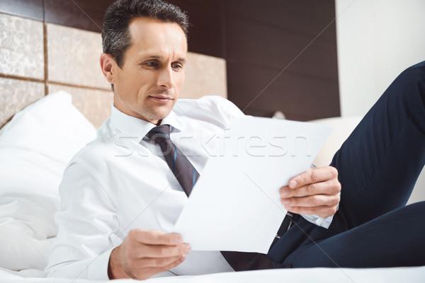 Businessman on bed reading paperwork Stock photo © LightFieldStudios