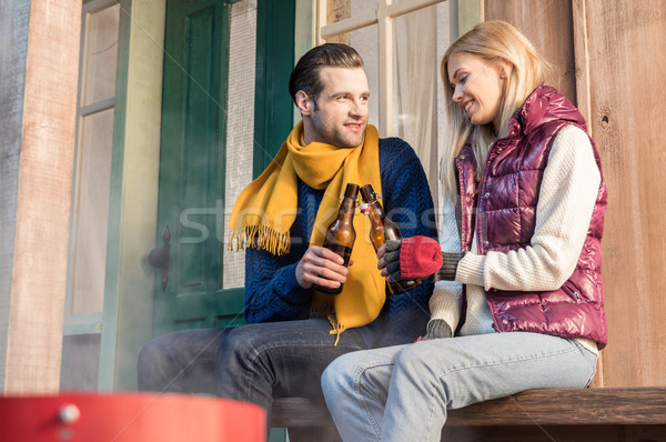 Happy young couple clinking beer bottles while sitting on wooden bench Stock photo © LightFieldStudios