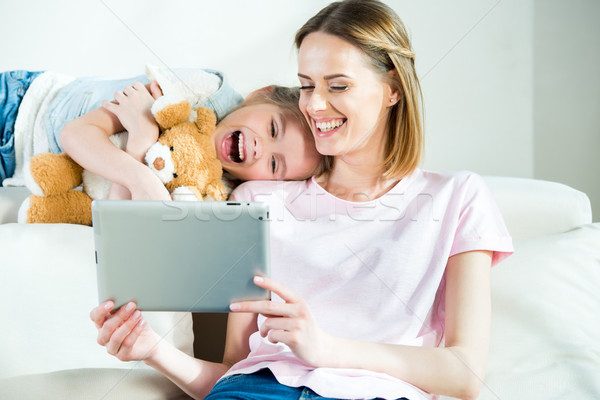 Happy mother and daughter with teddy bear using digital tablet at home Stock photo © LightFieldStudios