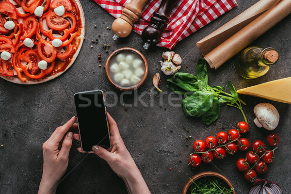 cropped shot of woman using smartphone while preparing pizza on concrete table Stock photo © LightFieldStudios