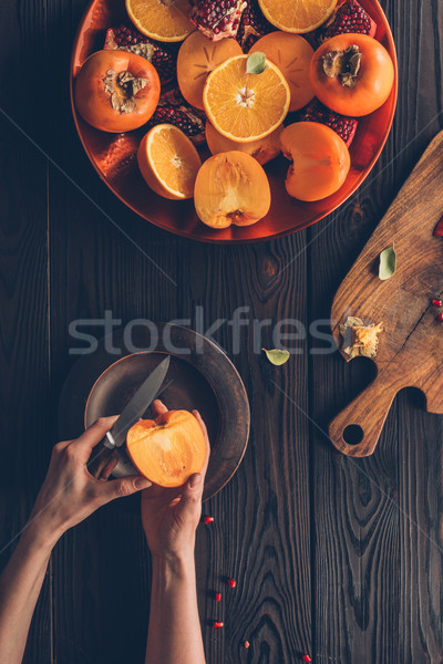cropped image of woman cutting persimmon Stock photo © LightFieldStudios