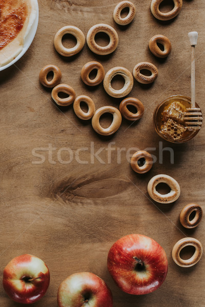 top view of sweet bagels, honey and apples on wooden table Stock photo © LightFieldStudios