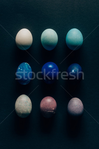 collection of nine colored painted easter eggs on dark surface Stock photo © LightFieldStudios