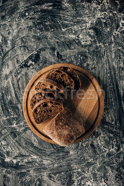 top view of arranged pieces of bread on cutting board on dark surface with flour Stock photo © LightFieldStudios