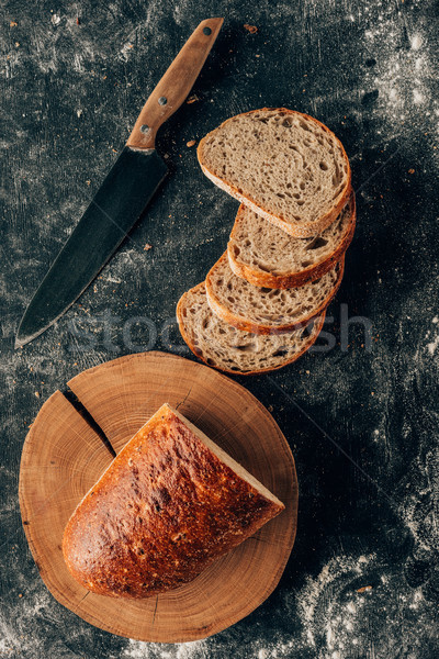 Stock photo: top view of arranged pieces of bread and knife on dark tabletop with flour