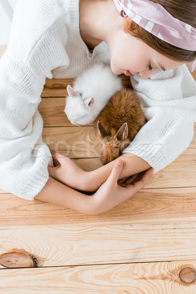 top view of girl hugging cute furry rabbits at wooden table Stock photo © LightFieldStudios