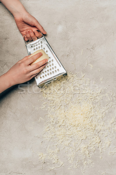 Close-up view of woman grating cheese on light background Stock photo © LightFieldStudios