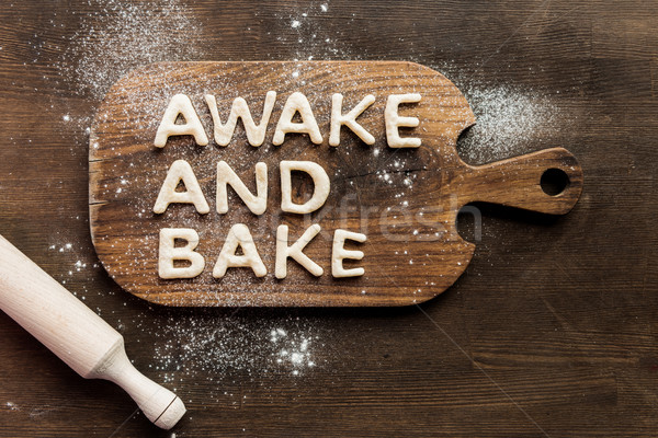 Top view of edible lettering awake and bake made from dough on wooden cutting board, baking cookies  Stock photo © LightFieldStudios