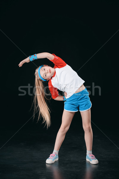 Cute sporty girl in sportswear exercising isolated on black, activities for children concept         Stock photo © LightFieldStudios