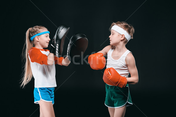 Side view of boy and girl in sportswear boxing isolated on black, activities for children concept Stock photo © LightFieldStudios