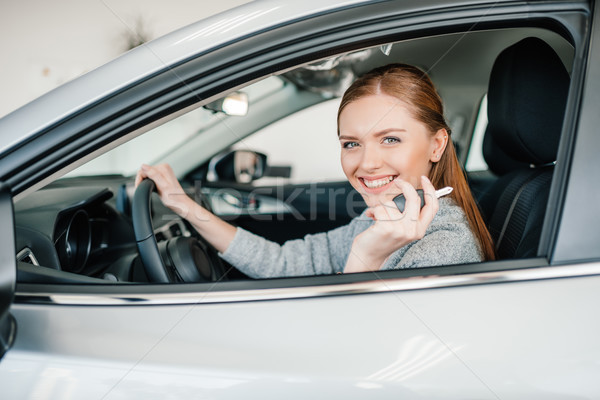 Happy young woman driver sitting in new car and holding key Stock photo © LightFieldStudios